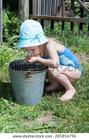 Little girl in a blue swimsuit sat at metal buckets and drinking water from their hands - stock photo