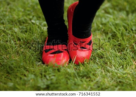 Little girl in a bright red shoes dancing on a green grass