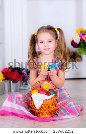little girl in a bright room in a colored dress holding Easter eggs in yellow and blue