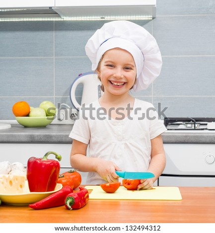little girl in a cap chef in the kitchen cutting tomatoes - stock photo