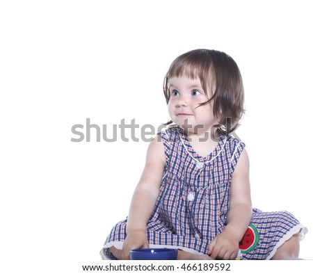 little girl in a checkered dress holding a mug isolated on white background
