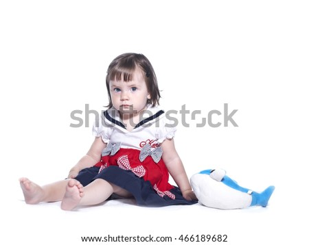 Little girl in a colorful dress. He is playing with a toy dolphin. Isolated on white background.