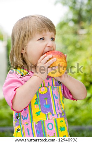 little girl in a coloured dress bites off an apple in the solar afternoon - stock photo