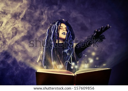 Little girl in a costume of witch casts a spell over magic book over dark background. - stock photo