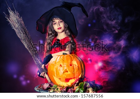 Little girl in a costume of witch posing with pumpkins over dark background.