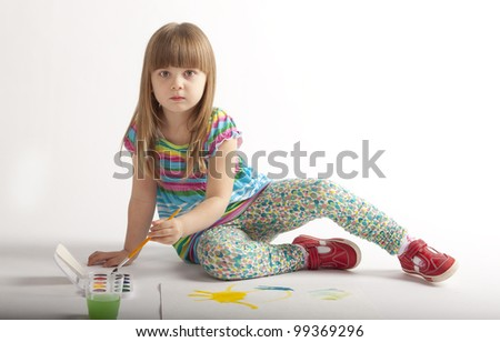 little girl in a dress the color paints paints sitting on the floor - stock photo