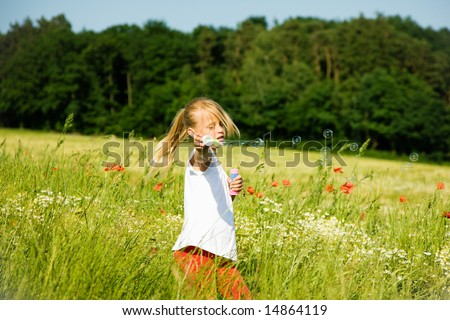 Little girl in a field making soap bubbles and having fun with it - stock photo