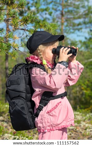 Little girl in a forest looking through binoculars - stock photo