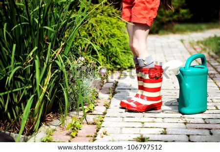 Little girl in a garden with green watering pot