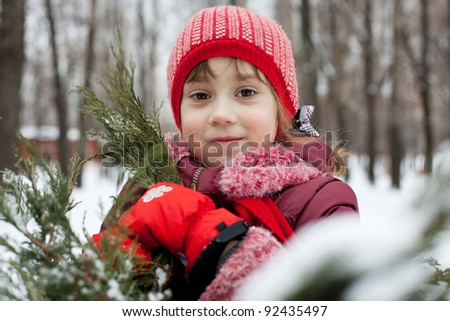 Little girl in a knitted hat next to Christmas tree