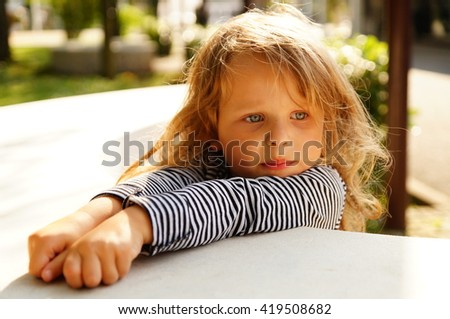 little girl in a park at a desk dreaming