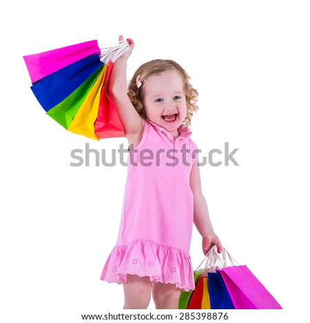 Little girl  in a pink dress holding colorful shopping bags. Child in a shop buying clothes. Sale in a store. Kids with purchases isolated on white background.