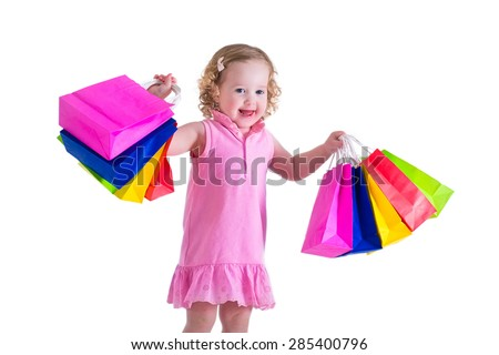 Little girl  in a pink dress holding colorful shopping bags. Child in a shop buying clothes. Sale in a store. Kids with purchases isolated on white background. - stock photo