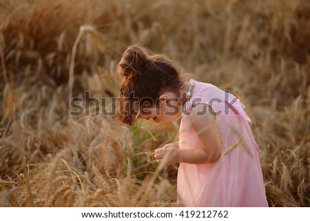 little girl in a pink dress leaned over wheat spikelets.
