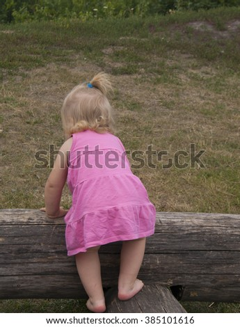 little girl in a pink dress on the wooden log - stock photo