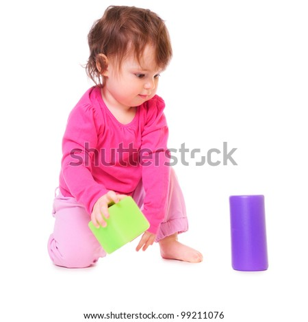 little girl in a pink dress, played with blocks and cubes. isolated on white - stock photo