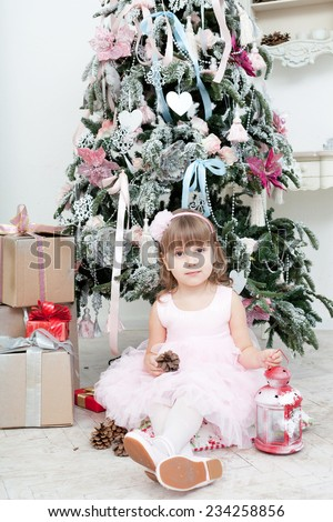 Little girl in a pink dress sits near a Christmas fir-tree