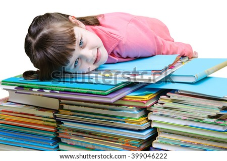 Little girl in a pink jacket lies on a pile of books - stock photo