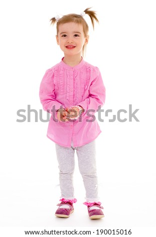 Little girl in a pink shirt standing on white background - stock photo