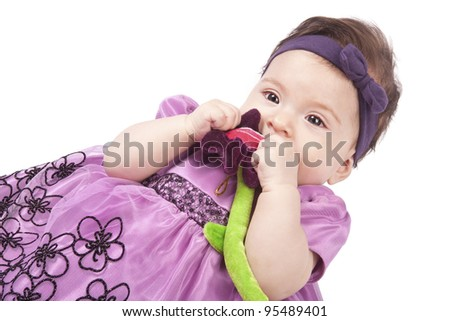 little girl in a purple dress with a brown patch over his head holding a plush flower and chewing it - stock photo