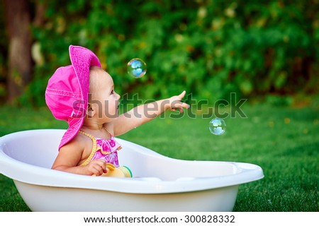 little girl in a red hat bathed in the bath. - stock photo