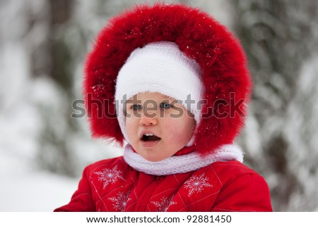 Little girl in a red winter suit and white cap - stock photo