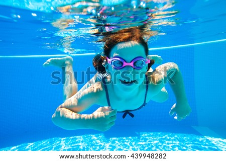 little girl in a striped bathing suit swims in the pool underwater - stock photo