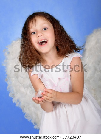 little girl in a suit of an angel on a blue background
