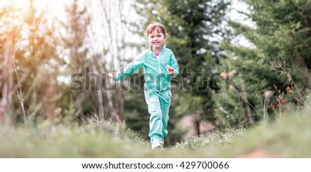 Little girl in a tracksuit running along the path in the woods