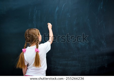 little girl in a white T-shirt with pigtails writing with chalk on chalkboard - stock photo