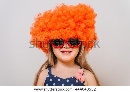little girl in a wig. orange wig. funny little girl in a dress, glasses and an orange wig. girl dressed in a dress and a wig. wig and glasses. - stock photo