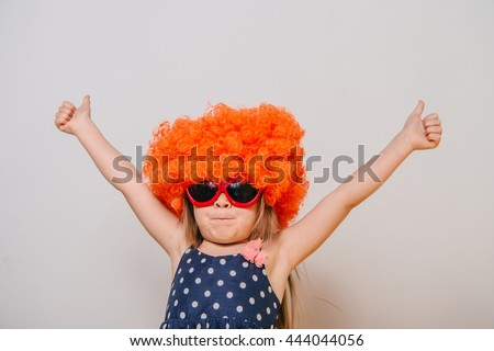 little girl in a wig. orange wig. funny little girl in a dress, glasses and an orange wig. girl dressed in a dress and a wig. wig and glasses. Girl shows gesture thumbs up - stock photo