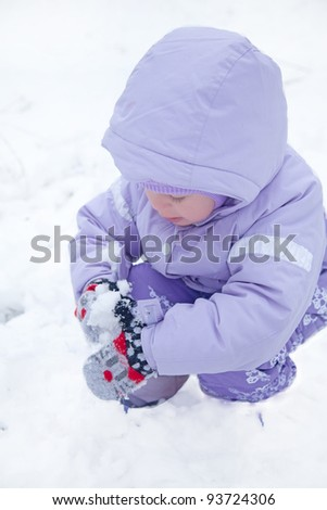 little girl  in a winter park with a snowball - stock photo