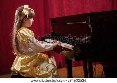 little girl in a yellow dress, playing classical music - stock photo