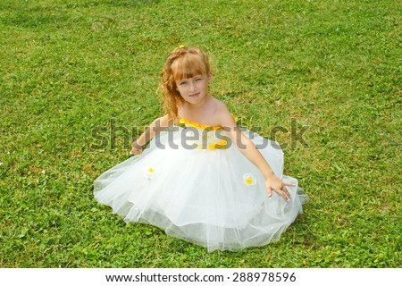 Little girl in a yellow festive dress on a green lawn - stock photo