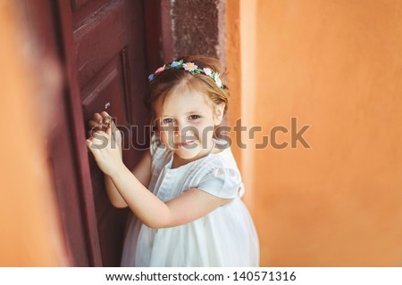 Little girl in an urban setting smiles at the camera. - stock photo
