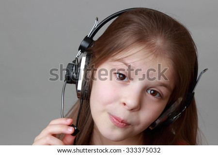 Little girl in beautiful red dress singing with headphone