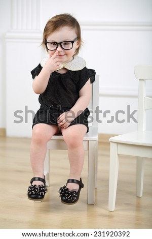 Little girl in black dress and glasses sitting on white chair and putting finger to nose - stock photo