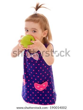 Little girl in blue dress biting an apple - stock photo