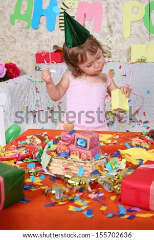 Little girl in cap drinks juice at table with cake at birthday party. Inscription Happy Birthday on wall.
