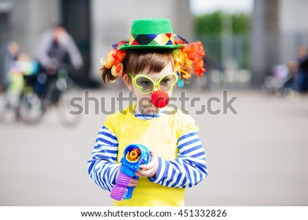 Little girl in clown costume blowing bubbles outdoors at summer day - stock photo