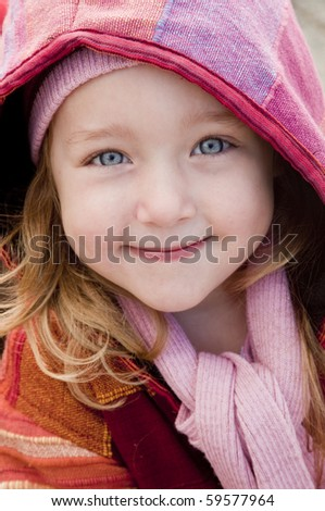Little girl in colorful winter clothes smiling at camera. - stock photo
