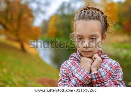 Little girl in demi-season coat on the background of autumn park. - stock photo