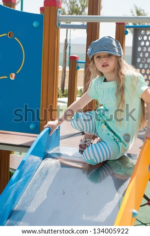 Little girl in denim peaky cap playing - stock photo
