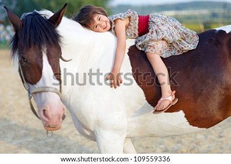 Little girl in  dress galloping on her white horse - stock photo
