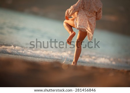 little girl in dress is jumping on the waves of the sea - stock photo