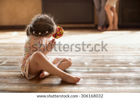 little girl in dress with long hair sitting on the wooden floor at home or studio and licking big candy - stock photo