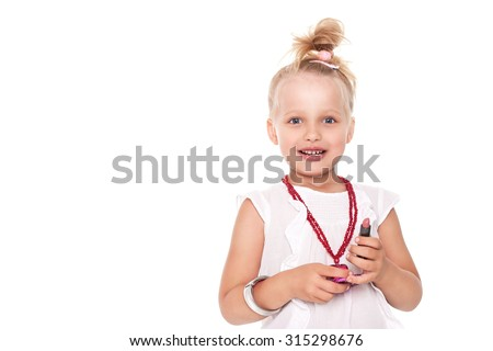 Little girl in fashionable clothes blond with a mirror and lipstick on a white space for writing - stock photo