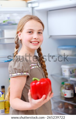 little girl in front of an open fridge holding red bell pepper