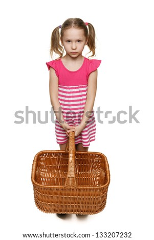 Little girl in full length holding empty wicker basket isolated on white background - stock photo